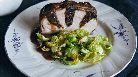Arrosto di maiale in crosta di pancetta con ripieno di prugne secche e contorno di cavoletti di Bruxelles