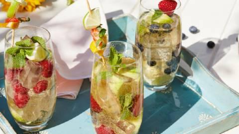 Cocktail di spumante estivo con limetta, frutti di bosco e menta