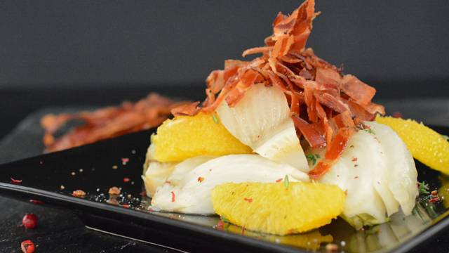 Finocchi stufati con arance e strisce di speck cotto al forno