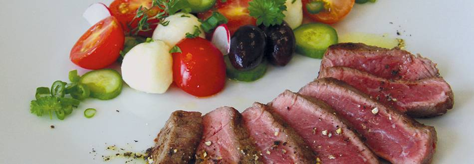 Entrecôte con insalata fresca di pomodori, mozzarella e olive