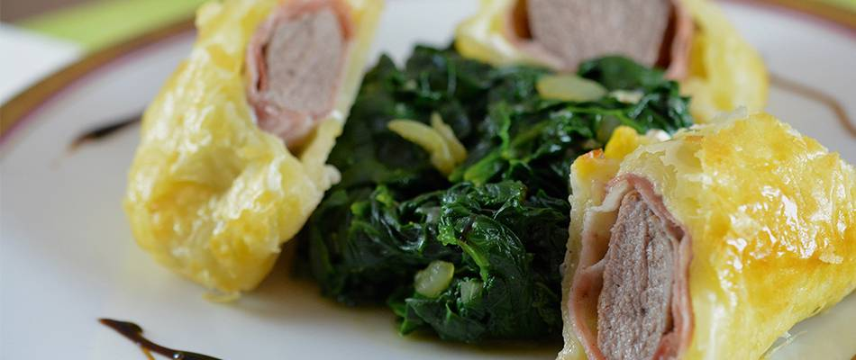 Filetto d'agnello con prosciutto crudo in pasta sfoglia, servito su letto di spinaci